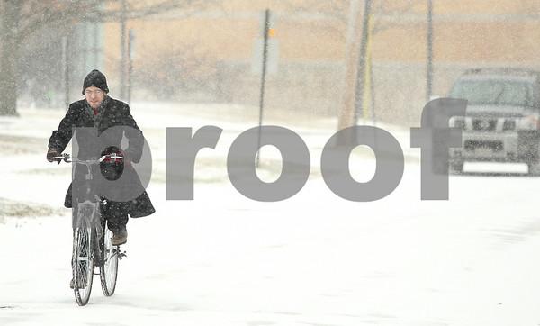 Kyle Bursaw – kbursaw@shawmedia.com<br /> <br /> Matthew Sirek, a senior at Northern Illinois, bikes on campus through the snowy conditions on Thursday, Jan. 12, 2012.