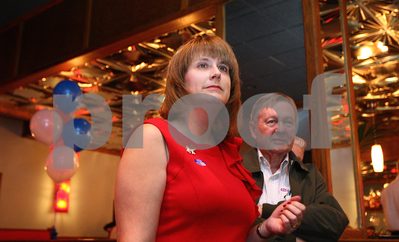 Kyle Bursaw – kbursaw@shawmedia.com<br /> <br /> State Senator Christine Johnson looks at  election results on a projection screen with supporter Charles Krull behind her at the Stratford Inn in Sycamore, Ill. on Tuesday, March 20, 2012.