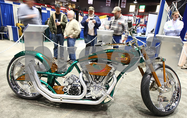 """Kyle Bursaw – kbursaw@shawmedia.com<br /> <br /> People at the Northern Illinois farm show stop to look at the motorcycle the DeKalb corn brand had designed by Paul Jr. Designs of Discovery Channel's """"American Chopper- Senior v. Junior,"""" to celebrate the company's 100th anniversary. The bike will be auctioned online starting Jan. 20, 2012, with proceeds going to the American Red Cross."""