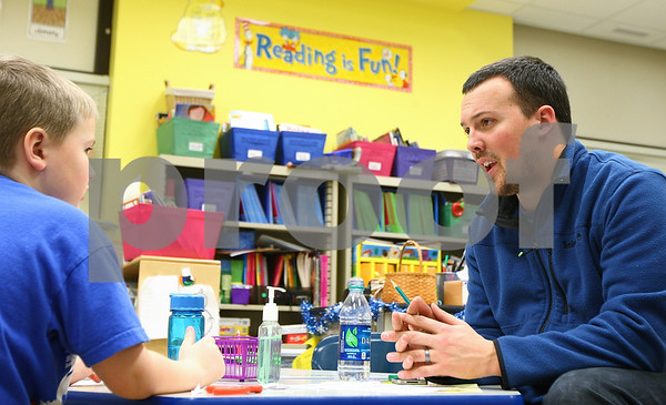Kyle Bursaw – kbursaw@shawmedia.com<br /> <br /> Jake Young (right) works with his son Carter Young, 6, on a word-building activity in Carter's classroom at Founders Elementary on the evening of Friday, Feb. 3, 2012.