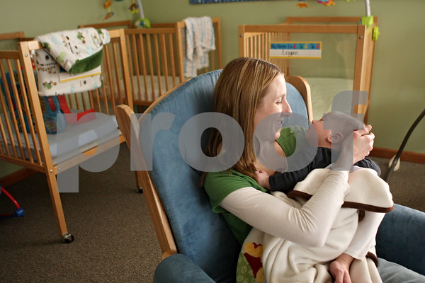 Rob Winner – rwinner@shawmedia.com<br /> <br /> Heather Zapatka of Walnut Street Daycare Center rocks 2-month-old Logan Limberg to sleep on Thursday afternoon in Genoa. The daycare, which opened in 2011, like several Genoa businesses is benefiting from a three-year tax-break package.<br /> <br /> Thursday, Jan. 19, 2012