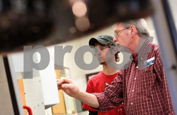 Kyle Bursaw – kbursaw@shawmedia.com<br /> <br /> Kishwaukee College computer-aided manufacturing instructor Bob Lawrence helps Rich Nelson, 21 (left), program a machine to produce a part on Wednesday, April 4, 2012. Nelson started learning about manufacturing when he took classes at the college for two years through the Kishwaukee Education Consortium program while a student a Genoa-Kingston High School.