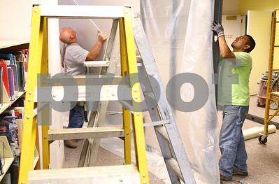 Kyle Bursaw – kbursaw@shawmedia.com  Joe Swedberg (left) and Carlos Perusquia, of Swedberg and Associates,  put up a temporary wall on the lower floor of the Sycamore Library as they begin work on the interior remodel on Monday, April 16, 2012.