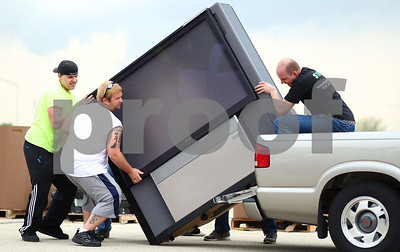 Kyle Bursaw – kbursaw@shawmedia.com  Justin and Jeramy Harkins (far left and right respectively) of Vintage Tech Recyclers along with the help of volunteers Jason Herring (white) and Matt Graziano (behind TV) remove a large television from the back of a truck in the Convocation Center parking lot during an event offering free recycling of electronics, held on Thursday, April 19, 2012.