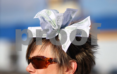 Kyle Bursaw – kbursaw@shawmedia.com  Marilyn Hrymak wears a bow of play money in her hair while protesting that the richest one percent pay more taxes at the DeKalb Post Office on Lincoln Highway on Tuesday, April 17, 2012. 'Millionaires Tax Day' protest was sponsored by Rebuild the American Dream DeKalb.