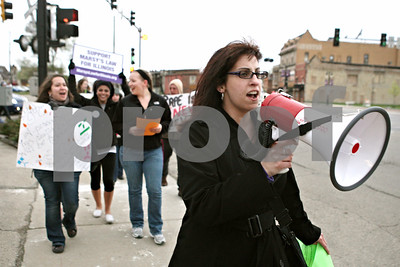 Rob Winner – rwinner@shawmedia.com  Amanda Schrems, sexual assault legal/medical advocate for Safe Passage, uses a megaphone to lead a chant Friday during Take Back the Night in downtown DeKalb.  Friday, April 20, 2012
