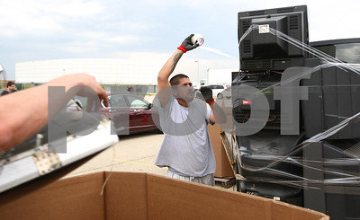 Kyle Bursaw – kbursaw@shawmedia.com  Lino Favela of Vintage Tech Recyclers tapes up a stack of televisions on a pallet as another worker tosses something into a cardboard container used to sort items at a free electronics recycling event held at Convocation Center on Thursday, April 19, 2012. The event was a joint effort between Habitat for Humanity of Illinois, Vintage Tech Recyclers and a business course at Northern Illinois University.