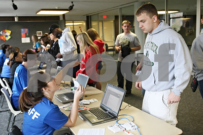 Rob Winner – rwinner@shawmedia.com  Northern Illinois University student Patrick Olas (right) checks in at the Holmes Student Center before starting a volunteer project during NIU Cares Day Saturday morning in DeKalb.