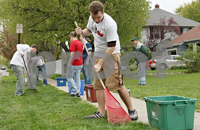 Rob Winner – rwinner@shawmedia.com  Northern Illinois University Sophomore Trevor McKeown (front) uses a rake while doing yard work for Dave Miner (right) during NIU Cares Day Saturday morning in DeKalb. Miner injured his shoulder five years ago and appreciated the help from the NIU students.