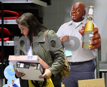 Kyle Bursaw – kbursaw@shawmedia.com  Lisa Nordman, of Oregon, Ill., looks through items for sale at the Convocation Center's Colossal Clean Sweep indoor garage sale as a cardboard cutout of Windell Middlebrooks as the Miller Delivery guy stands behind her on Friday, April 20, 2012.