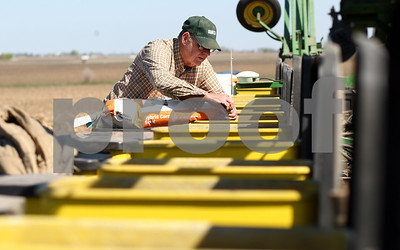 Kyle Bursaw – kbursaw@shawmedia.com  Paul Schweitzer unloads bags of corn seed into the bins of a seed planter while planting at a Malta farm on Thursday, April 12, 2012.