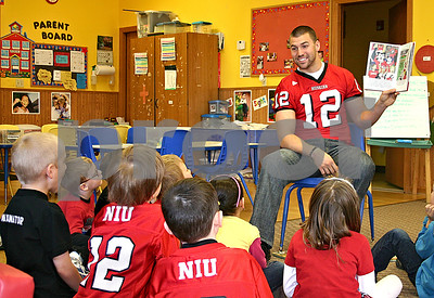 "Chandler Harnish, quarterback for the Northern Illinois University Huskies, reads ""Hello Victor E. Huskie"" to 5-year-olds at Land of Learning Child Care Center in Sycamore Monday.  By Nicole Weskerna - nweskerna@shawmedia.com"