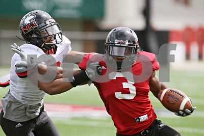 Rob Winner – rwinner@shawmedia.com  Northern Illinois cornerback Sean Evans (left) attempts a tackle of running back Akeem Daniels (3) during the Huskies' spring game Saturday in DeKalb.