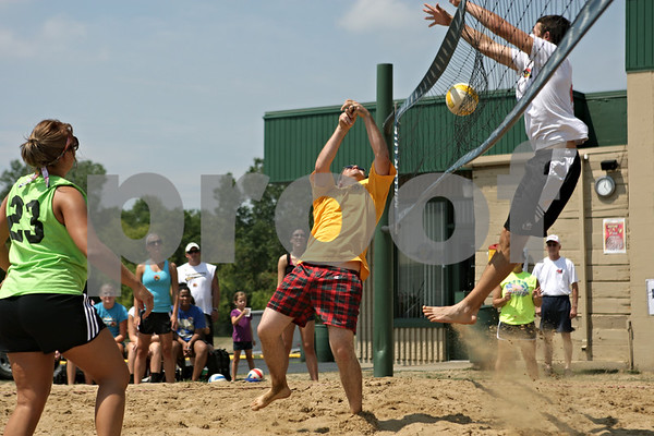 Rob Winner – rwinner@shawmedia.com<br /> <br /> DeKalb firefighter paramedic Greg Thornton (center) attempts to bump a ball over the net during a sand volleyball tournament outside Four Seasons Sports in Sycamore Saturday afternoon.  DeKalb Firefighters from the International Association of Fire Fighters Local 1236 hosted the sand volleyball tournament to benefit the Muscular Dystrophy Association.