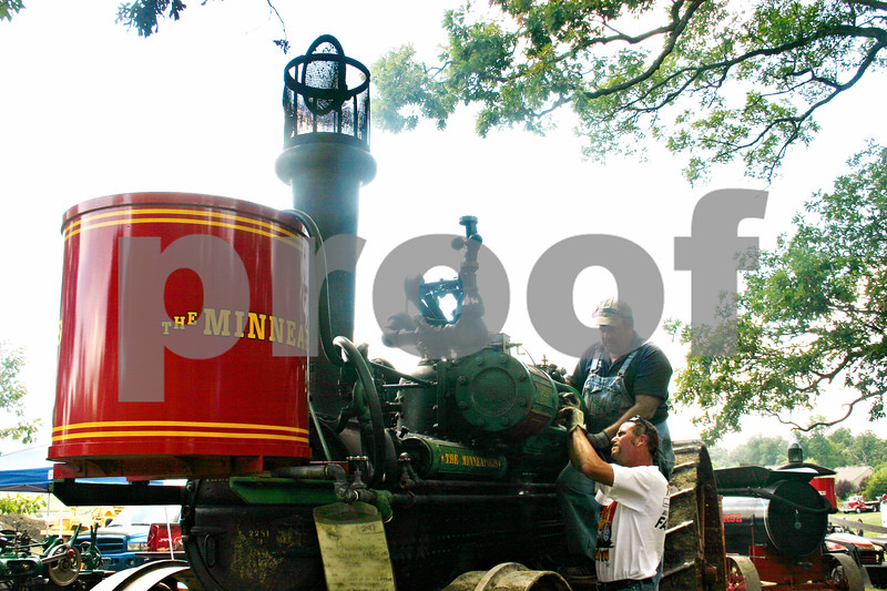 Caitlin Mullen – cmullen@shawmedia.com<br /> <br /> Charlie Hendrickson (top) and Ron Finster, both of Janesville, Wis., do some minor repairs to a 20-horsepower Minneapolis steam engine at the Sycamore Steam Show and Threshing Bee at the Taylor Marshall farm. The show began Thursday and ends Sunday.