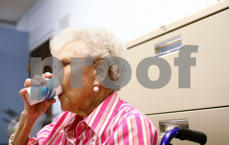 Kyle Bursaw – kbursaw@shawmedia.com<br /> <br /> Dorothy Rosene, 83, washes down her medication in Oak Crest's personal care office on Tuesday, Aug. 7, 2012. Since July 1 when the Illinois Cares Rx was discontinued, seniors on Medicare Part D like Rosene have had to pay more for their prescriptions.