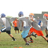 Kyle Bursaw – kbursaw@shawmedia.com<br /> <br /> Genoa-Kingston's Sal Lopez reaches out to wrap up Jamaal Williams (center) at practice on Thursday, Aug. 9, 2012.