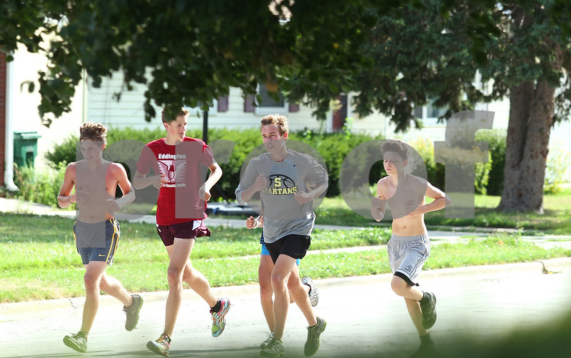 Kyle Bursaw – kbursaw@shawmedia.com<br /> <br /> Sycamore cross country runners including David Emmert (second from left) and Mark Stice (third from left) do a cool down run on Esther Avenue on Friday, Aug. 10, 2012.