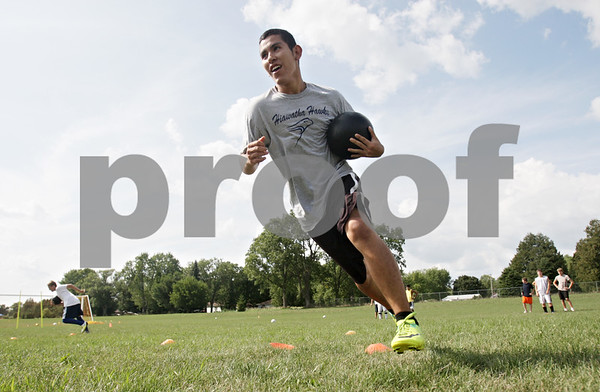 Rob Winner – rwinner@shawmedia.com<br /> <br /> Ed Canchola of Hiawatha carries a medicine ball while running a drill at practice in Kirkland, Ill., Tuesday, Aug. 14, 2012.