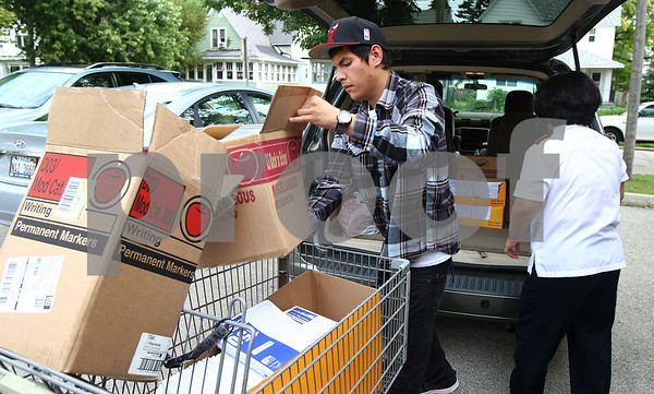 Kyle Bursaw – kbursaw@shawmedia.com<br /> <br /> Volunteer Justin Roscelli, 19, and Salvation Army co-captain Alisha Cho load school supplies into a shopping cart to move into the building. Roscelli and other volunteers would then load the supplies into backpacks that were distributed to families on Wednesday, Aug. 15, 2012.