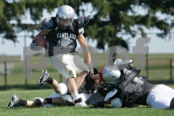 Rob Winner – rwinner@shawmedia.com<br /> <br /> Kaneland running back Dan Goress is hit after a reception during a scrimmage at practice in Maple Park, Ill., Saturday, Aug. 11, 2012.