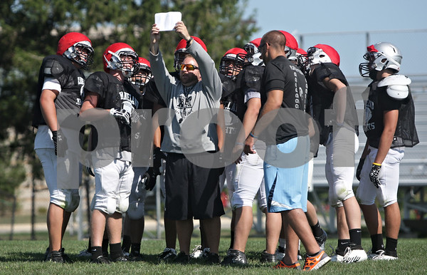 Rob Winner – rwinner@shawmedia.com<br /> <br /> Kaneland defensive coordinator Keith Snyder holds up a play for the defense during a scrimmage at practice in Maple Park, Ill., Saturday, Aug. 11, 2012.