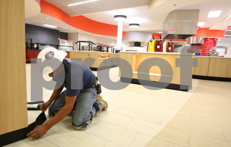 Kyle Bursaw – kbursaw@shawmedia.com<br /> <br /> Chamo Capellan works on putting the final touches to the base of one of the structures in the food court area of the center building of the new residential complex at Northern Illinois University on Monday, Aug. 13, 2012.