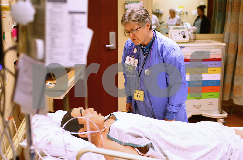 Kyle Bursaw – kbursaw@shawmedia.com<br /> <br /> Cheryl Moberg talks to a high-fidelity mannequin during a simulation exercise<br /> at Kishwaukee Community Hospital's on Thursday, Aug. 16, 2012. The simulation patient, who could also speak back to Moberg, is controlled by staff from the other side of a one-way mirror (background).