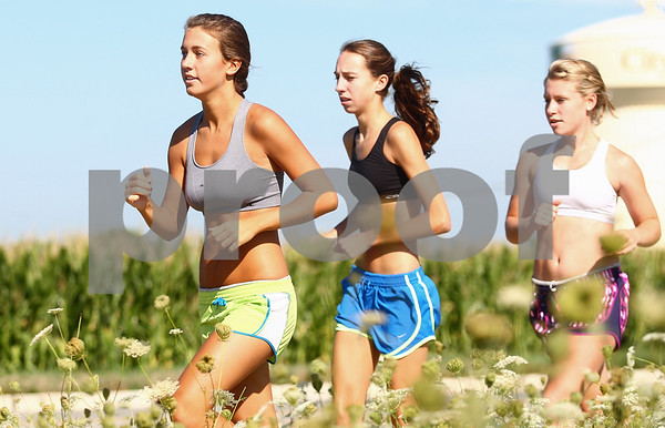 Kyle Bursaw – kbursaw@shawmedia.com<br /> <br /> DeKalb cross country runners (from left) Marissa Maeder, Sara Schafer and Malerie Meares run on Normal Road during practice on Tuesday, Aug. 14, 2012.