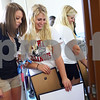 Kyle Bursaw – kbursaw@shawmedia.com<br /> <br /> Taylor Jacques (right) shows roommate Angela Versluis pictures of the two of them she plans to put up on her wall when they are allowed to in a month while unpacking their rooms in New Residence Hall on Thursday, Aug. 23, 2012.