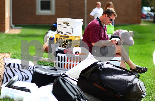 Kyle Bursaw – kbursaw@shawmedia.com<br /> <br /> Bob Coyne checks his cell phone while sitting on the lawn outside of New Residence Hall with his daughter Sam Coyne's belongings while she goes through the check in process on Thursday, Aug. 23, 2012.