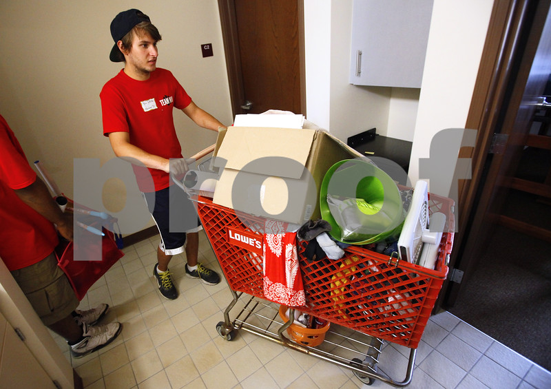 Kyle Bursaw – kbursaw@shawmedia.com<br /> <br /> Danny White, a volunteer through his fraternity, Sigma Alpha Epsilon, pushes a shopping cart full of a student's possessions while helping her move into  New Residence Hall East on Thursday, Aug. 23, 2012