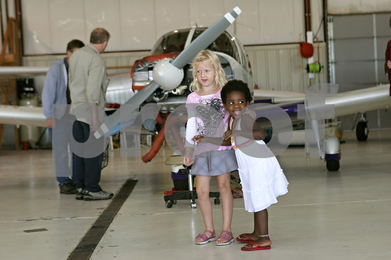 Rob Winner – rwinner@shawmedia.com<br /> <br /> Kaylee Skeens (left), 4, of Cortland, and Ava Wilkins, 3, of Sycamore, play together inside a hangar at the DeKalb Taylor Municipal Airport while their siblings participate in a Young Eagles flight on Saturday, Aug. 18, 2012, in DeKalb, Ill.