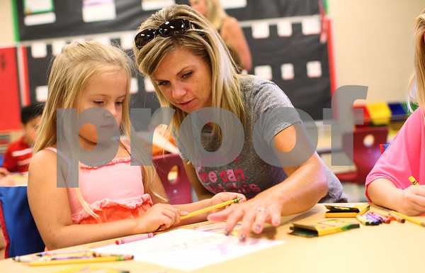 Kyle Bursaw – kbursaw@shawmedia.com<br /> <br /> On the first day of school Tami Burgess helps her daughter Bella, 6, work on a drawing of something she did over the summer. Bella drew about her trip to SeaWorld to share with the rest of Kelly Wright's first grade class at North Grove Elementary in Sycamore, Ill. on Wednesday, Aug. 22, 2012.