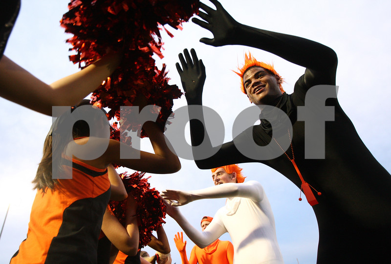 Kyle Bursaw – kbursaw@shawmedia.com<br /> <br /> DeKalb fans Andre Harris (black suit, front), Jordan Rossdeutcher (white suit) and Nick Bourdages (orange suit, far back) high five girls on the Poms squad as they move in position for the football team's entrance before the varsity game against Hampshire on Friday, Aug. 31, 2012.
