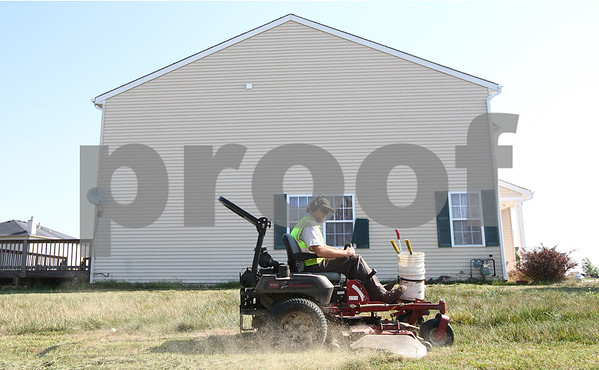 Kyle Bursaw – kbursaw@shawmedia.com<br /> <br /> Paul Naugle, Kirkland's public works superintendent, mows the lawn outside a foreclosed home on the corner of Cottonwood Boulevard and Kennedy Drive on Thursday, Aug. 30, 2012.