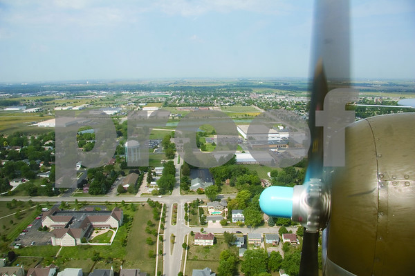 """Curtis Clegg - cclegg@shawmedia.com<br /> The Sycamore cityscape passes below a propeller of the World War II-era B-25 bomber """"Miss Mitchell"""" on Friday, August 24, 2012. The B-25 will be part of the air fest at the DeKalb Taylor Municipal Airport during Corn Fest through Sunday afternoon."""