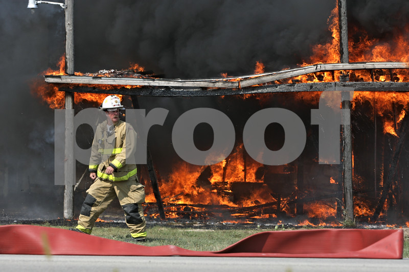 Rob Winner – rwinner@shawmedia.com<br /> <br /> Maple Park Fire Chief Kevin Peterson walks near a barn on fire located on West Lincoln Highway in DeKalb, Ill., Saturday, Aug. 25, 2012.