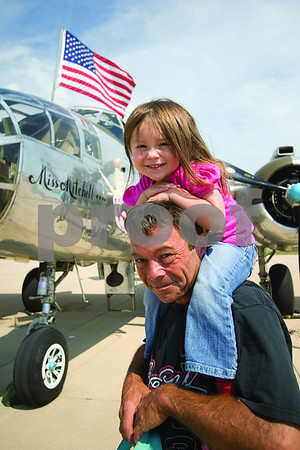 """Curtis Clegg - cclegg@shawmedia.com<br /> Stella Meyer, 3, of Hampshire with her grandfather Dean Meyer in front of the B-25 Bomber """"Miss Mitchell"""" at DeKalb Taylor Municipal Airport on Friday, August 24, 2012. The B-25 will be part of the air fest at the airport during Corn Fest through Sunday afternoon."""