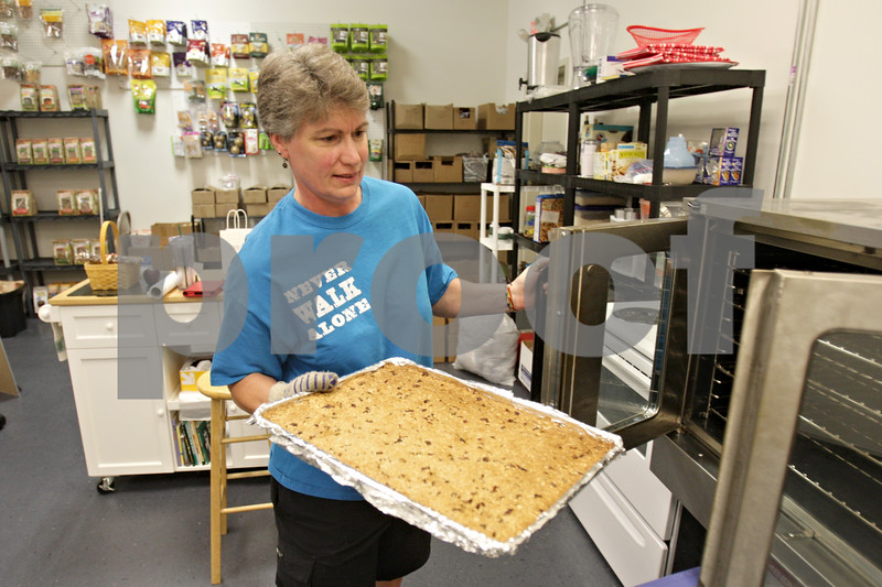 Rob Winner – rwinner@shawmedia.com<br /> <br /> Paw Lickin' Good owner Jody Meerdink removes a pan of cooked granola from an oven in the kitchen area of her business in Sycamore Thursday afternoon.