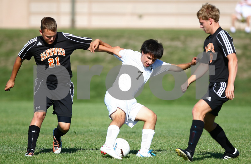 Kyle Bursaw – kbursaw@shawmedia.com<br /> <br /> Sycamore's Ivan Chavez battles for the ball with Sandwich player Colton Beatty (21) as another Sandwich player approaches during the first half at Sycamore High School on Monday, Aug. 27, 2012.