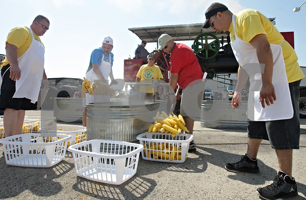 Rob Winner – rwinner@shawmedia.com<br /> <br /> Mike Craft (left) and Ammar Mahmood use silage forks to gather steamed sweet  corn for guests to Corn Fest Saturday afternoon at the DeKalb Taylor Municipal Airport. <br /> <br /> Saturday, Aug. 25, 2012<br /> DeKalb, Ill.<br /> <br /> **Craft is in blue and Mahmood is in red**