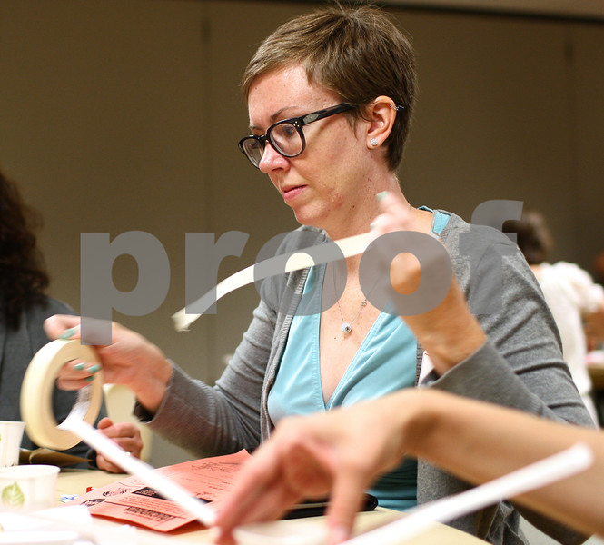 """Kyle Bursaw – kbursaw@shawmedia.com<br /> <br /> Peggy Keiner, the instructional technology coach with the Oak Lawn-Hometown school district, rips off some tape while using household materials to create an emergency landing device for her 'astronauts' made of marshmallows, an activity in the """"Boosting Girls' Interest in Engineering"""" seminar in the Holmes Student Center on Monday, Aug. 27, 2012."""