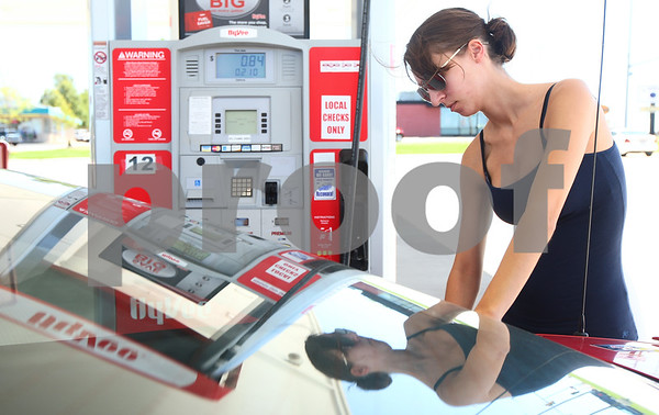 Kyle Bursaw - kbursaw@shawmedia.com<br /> <br /> Hannah Brennan, 18, from Hinckley, fills up her tank at Hy-Vee in Sycamore on her way home from work on Monday, Aug. 6, 2012.
