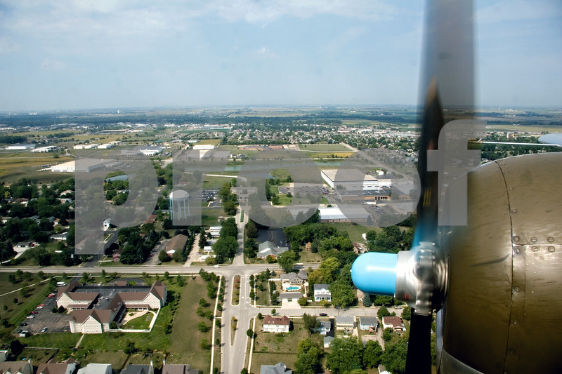 """Curtis Clegg - cclegg@shawmedia.com<br /> <br /> The Sycamore cityscape passes below a propeller of the World War II-era B-25 bomber """"Miss Mitchell"""" on Friday, August 24, 2012. The B-25 will be part of the air fest at the DeKalb Taylor Municipal Airport during Corn Fest through Sunday afternoon."""