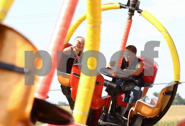 Kyle Bursaw – kbursaw@shawmedia.com<br /> <br /> DeKalb residents (from left) Shanna MacNeille, 12, and Dominick Allen, 10, ride the tornado at Corn Fest on Friday, Aug. 24, 2012.
