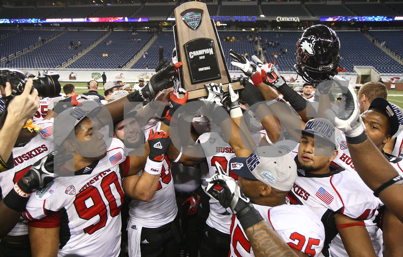 Kyle Bursaw – kbursaw@shawmedia.com<br /> <br /> Northern Illinois University players all grab for a piece of their MAC conference championship trophy after the Huskies 44-37 overtime victory over Kent State in the MAC conference championship game at Ford Field in Detroit, Mich. on Friday, Nov. 30, 2012.
