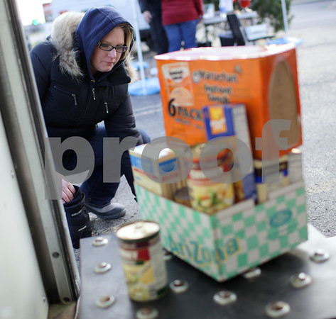 Kyle Bursaw – kbursaw@shawmedia.com<br /> <br /> Alison Taylor, of the WBLK sales department, weighs in a donation of food during the annual Freezin' for Food drive where they will be taking non-perishable  donations until noon Saturday in the Target/Aldi shopping center near Starbucks in DeKalb, Ill. on Wednesday, Dec. 5, 2012.