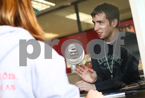 Kyle Bursaw – kbursaw@shawmedia.com<br /> <br /> Max Witthoeft, an NIU student and Convocation Center employee, explains to students turning in forms on Monday, Dec. 3, 2012 to get their free tickets to the Discover Orange Bowl that they will need their NIU OneCard to pick up the tickets on the day of the game in Miami.