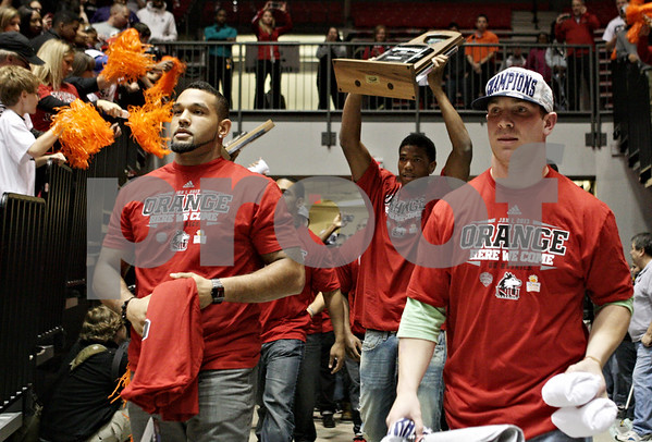 Rob Winner – rwinner@shawmedia.com<br /> <br /> Members of the Northern Illinois football team including Sean Progar (from left), Rashaan Melvin, and Jordan Lynch head out onto the basketball court at the Convocation Center in DeKalb during a pep rally Wednesday, Dec. 5, 2012.